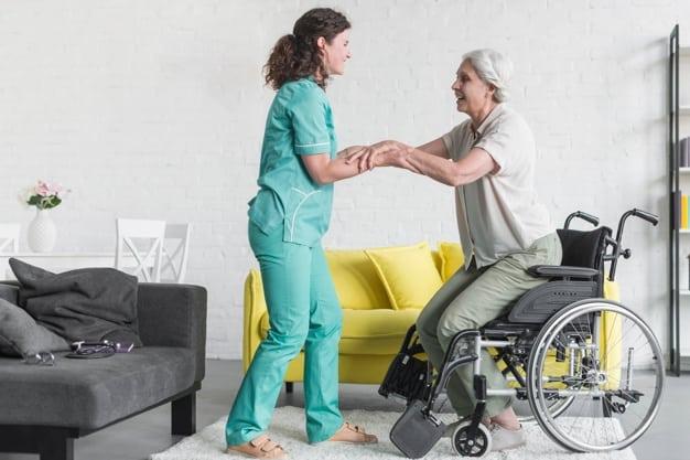l-infermiere-che-tiene-ha-disattivato-la-mano-della-donna-senior-che-si-siede-sulla-sedia-a-rotelle_23-2147861521